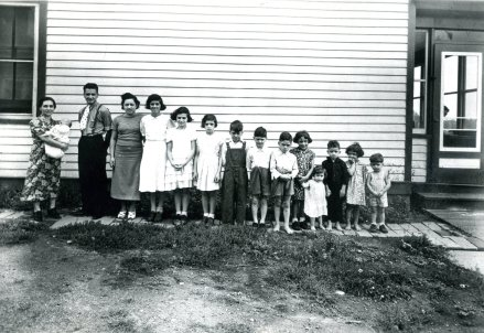 Note the boy peeking out the screen door - uncle George.  Dad is in the middle of the line-up wearing the bib overals